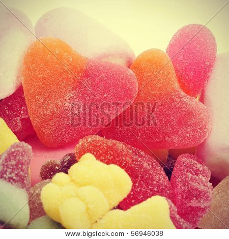 a pair of heart-shaped candies in a pile of different candies, with a retro effect