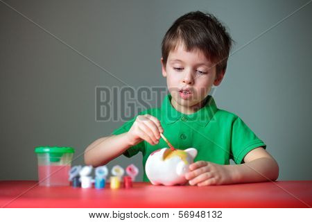 Cute little boy diligently painting his piggy toy