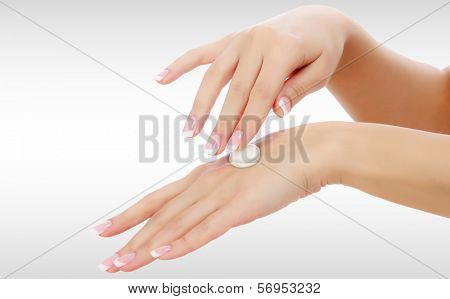 Female hands with a moisturiser on light grey background