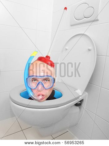 Funny picture from hotel bathroom. Crazy scuba diver in the toilet bowl.