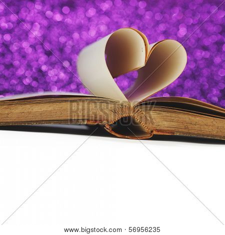 Heart made of blank pages inside a book on glitter background