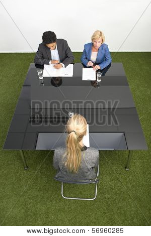 Applicant sitting across a black, glass, conference table with two senior human resource managers during a job interview