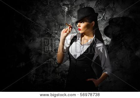 Dangerous and beautiful criminal girl with cigar on grey wall