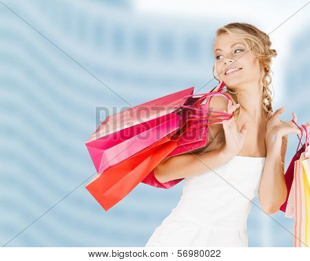 retail and sale concept - elegant woman in dress with shopping bags
