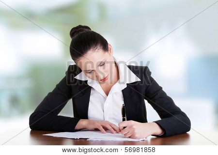 Beautiful attractive corporate lawyer business woman sitting at desk and writing blank paper page.