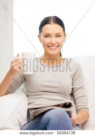 home and leasure concept - smiling woman with cup of coffee or tea reading magazine at home