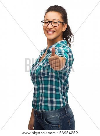 hapiness and people concept - smiling young african american woman in eyeglasses showing thumbs up