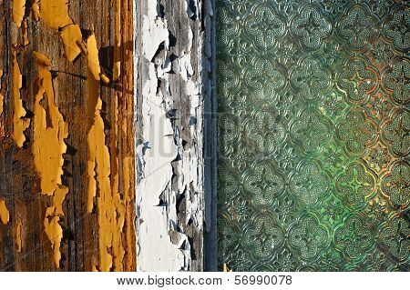 An old wooden house window with pealing off paint and old decorated window glass