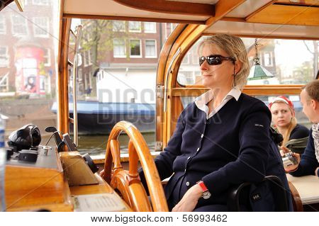AMSTERDAM, NETHERLANDS - 18 MAY: woman drive boat on canals of Amsterdam on 18 May 2009 in Amsterdam, Netherlands. Amsterdam is the capital and most populous city of the Netherlands.