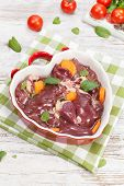 picture of giblets  - Raw chicken liver in heart shaped bowl. High angle view. ** Note: Shallow depth of field - JPG