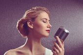 stock photo of singer  - attractive female singer with a microphone - JPG