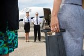 Full length of pilot and airhostess standing near private jet with business people in foreground