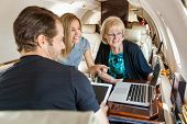 Businesswoman pointing at laptop to colleagues while working in private jet