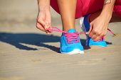 stock photo of shoe  - Female runner getting ready for running challenge workout on beach - JPG