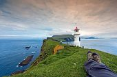 stock photo of faroe islands  - Landscape of Mykines Lighthouse with photographer - JPG