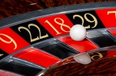 picture of roulette table  - Classic casino roulette wheel with red sector eighteen 18 and white ball and sectors 9 22 29 7 - JPG