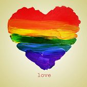 stock photo of gay flag  - the word love and a rainbow heart painted on a beige background - JPG