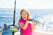 stock photo of troll  - Blond kid girl fishing tuna bonito sarda fish happy with trolling catch on boat deck - JPG