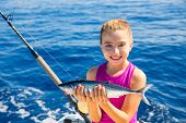 stock photo of troll  - kid girl fishing tuna bonito sarda fish happy with trolling catch on boat deck - JPG