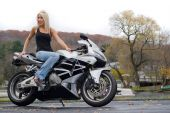 stock photo of crotch-rocket  - A pretty blonde girl posing on a motorcycle - JPG