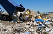 stock photo of dumpster  - View of truck dumping trash in landfill - JPG