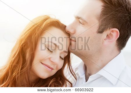 Young happy couple in love in a romantic moment of man kissing his wife in a forehead on the beach in summer sunshine.