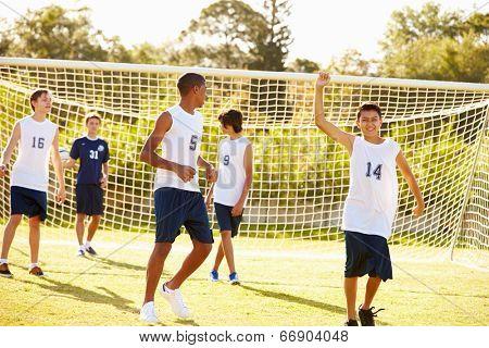 Player Scoring Goal In High School Soccer Match