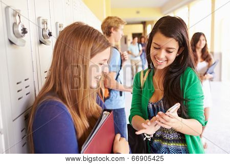 High School Students By Lockers Looking At Mobile Phone