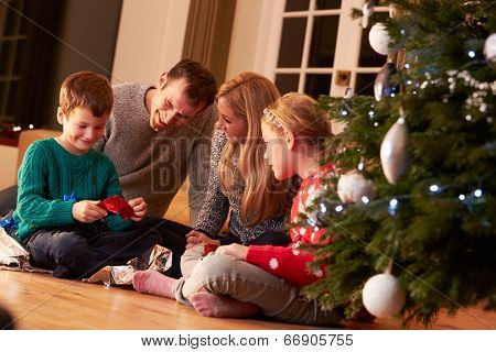 Family Unwrapping Gifts By Christmas Tree