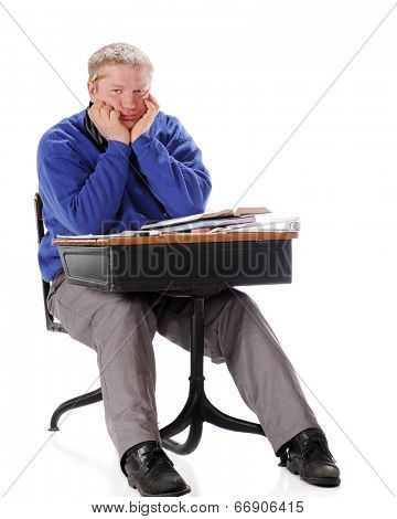 A bored mature man sitting in an old school desk piled with books and papers.  On a white background.