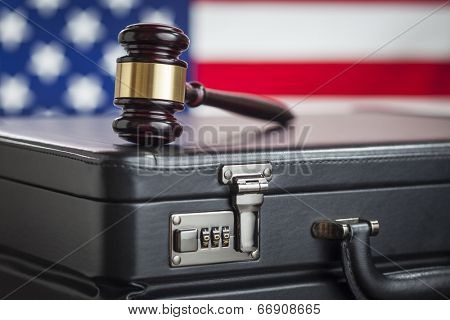 Leather Briefcase and Gavel Resting on Table with American Flag Behind.