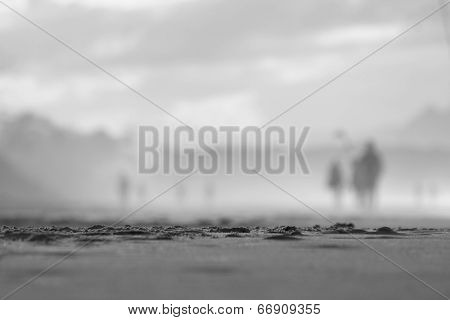 Black and White. soft focus people walking on beach 2