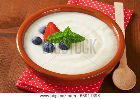 bowl of semolina pudding with wooden spoon