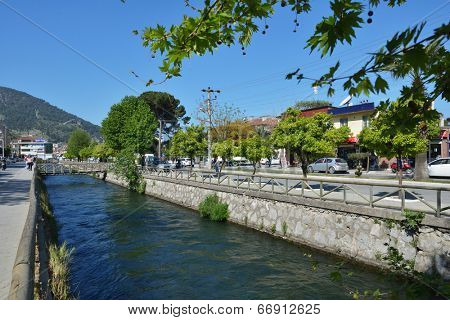 FETHIYE, TURKEY - APRIL 1, 2014: People and car traffic on the banks of river along the Ataturk Avenue. Fethiye is Turkey's well-known tourist centers and is especially popular during the summer