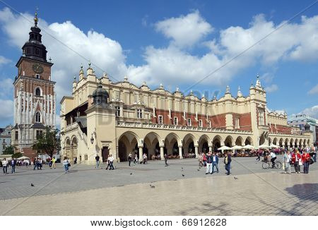 KRAKOW, POLAND - SEPTEMBER 15, 2013: People on the Main Market Square near Sukiennice, Cloth Hall, and the Town Hall tower. The Cloth Hall was built in XIV century, and now hosts souvenir shops