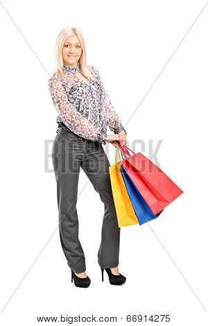 Full length portrait of a trendy girl holding shopping bags isolated on white background