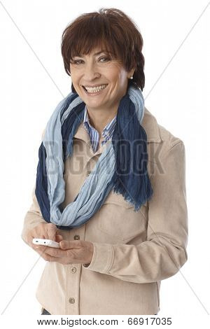 Elderly woman using mobilephone, smiling, looking at camera.