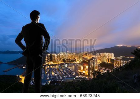 Asian businessman standing in the hill and looking at the skyscrapers and harbor in Aberdeen, Hong Kong, Asia.