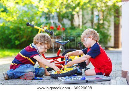Two Little Sibling Boys Repairing Broken Bike