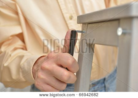 Man assembling the step stool. Selective focus on the Allen key