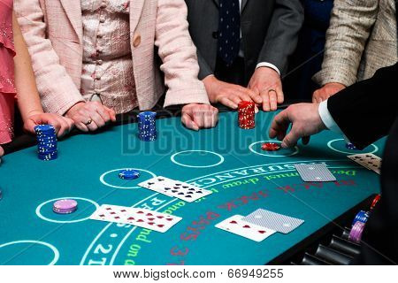 People placing bets on Black Jack card game