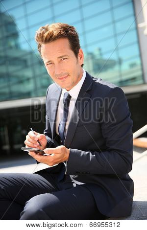 Businessman sitting outside and checking on timetable