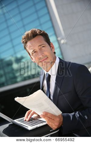 Businessman working on laptop computer outside the office