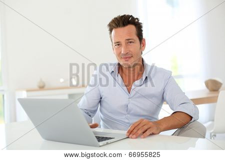 40-year-old man using laptop computer at home
