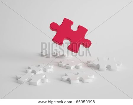 Leadership, solution and quality concept with a single different large red puzzle piece suspended above several smaller white puzzle pieces lying flat on a grey background