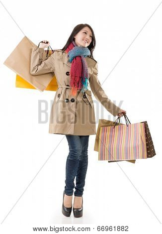 Winter shopping woman of Asian holding bags, full length portrait isolated on white background.