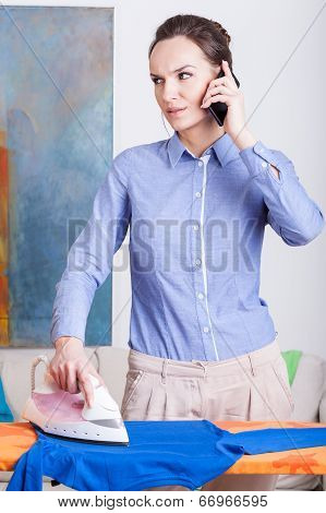 Woman Ironing Clothes And Talking On The Mobile Phone