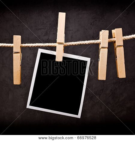 Photography Paper With Instant Photo Frame Attached To Rope With Clothes Pins.