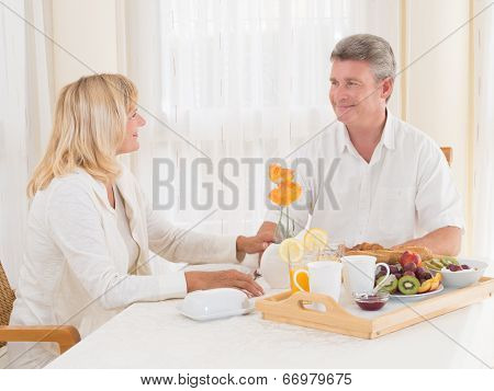 Loving Mature Couple Enjoying A Healthy Breakfast Smiling At Each Other