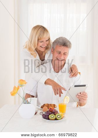 Happy Mature Couple At The Breakfast Pointing On Tablet Computer